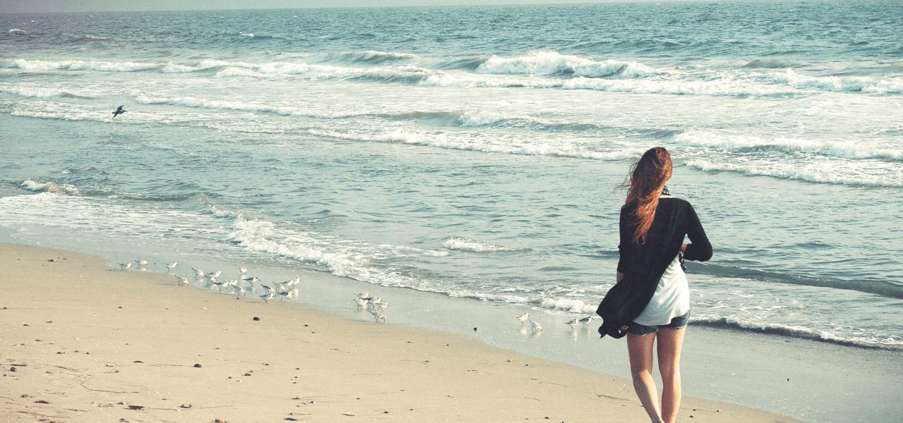 海を歩く海外の女性