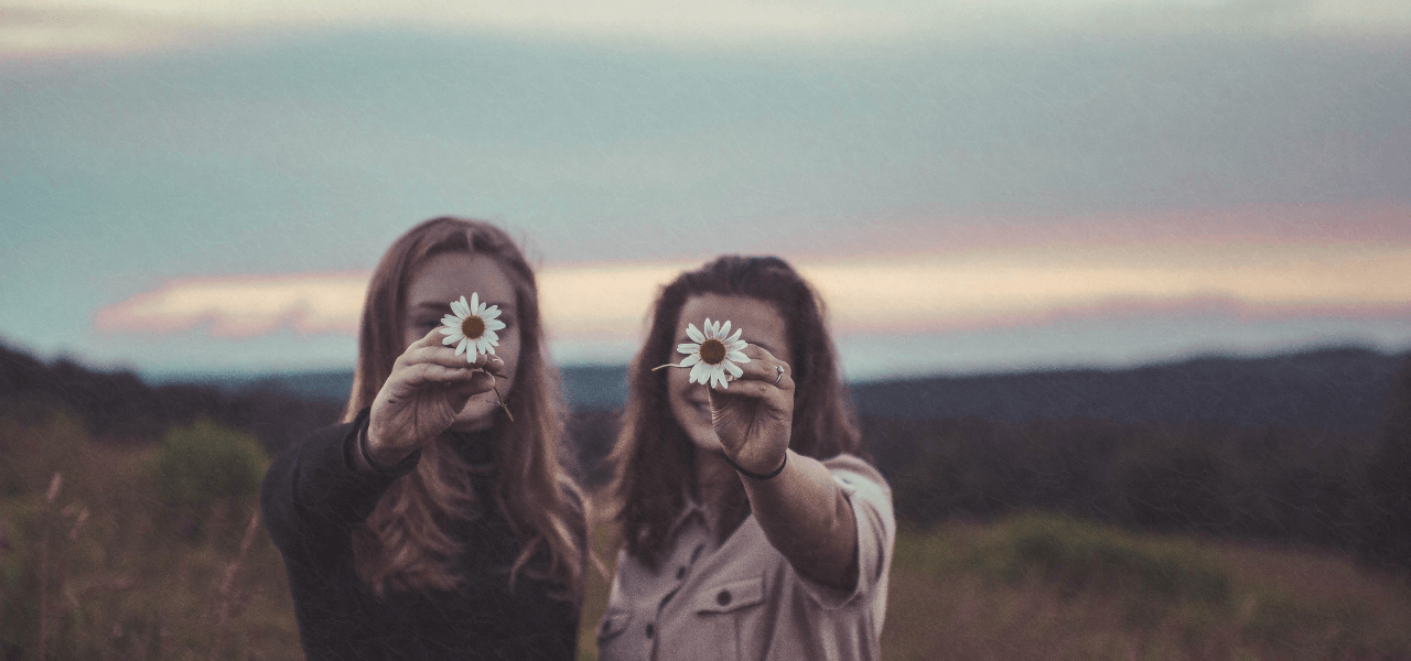 仲良く2つの花を顔の前に掲げる女性