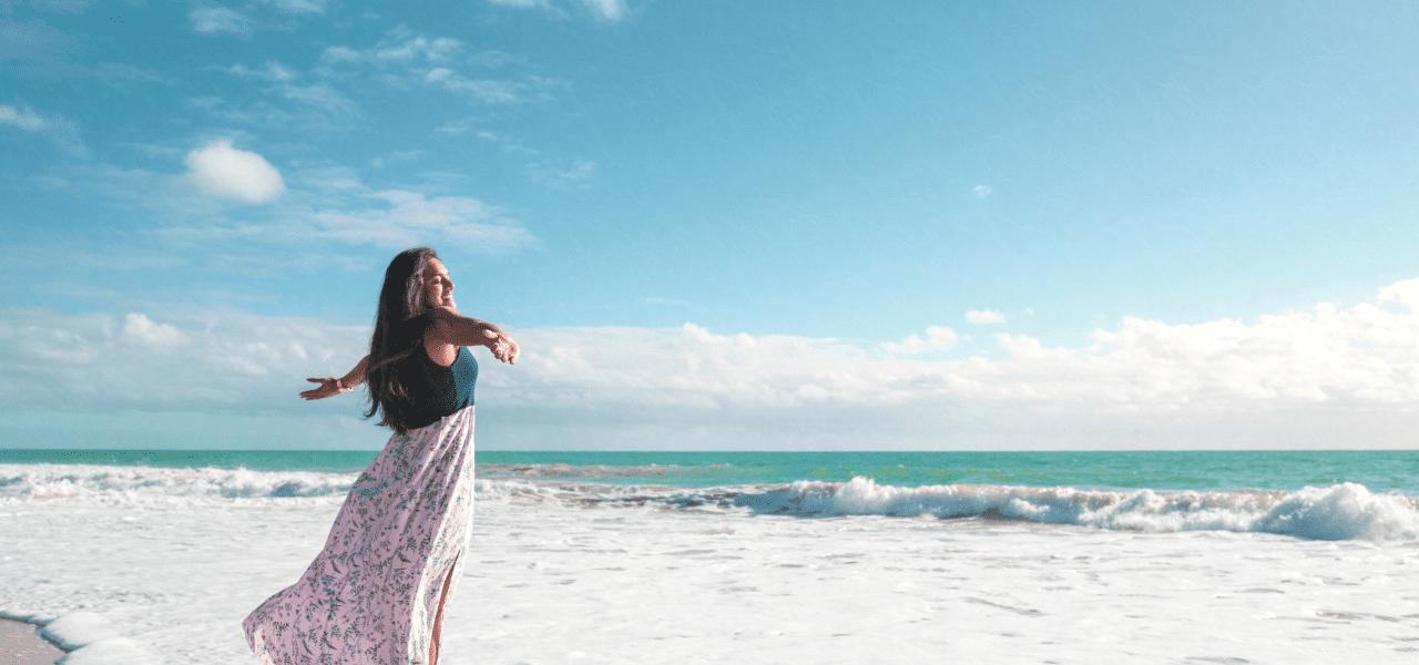 女性が海岸線で風を感じる様子