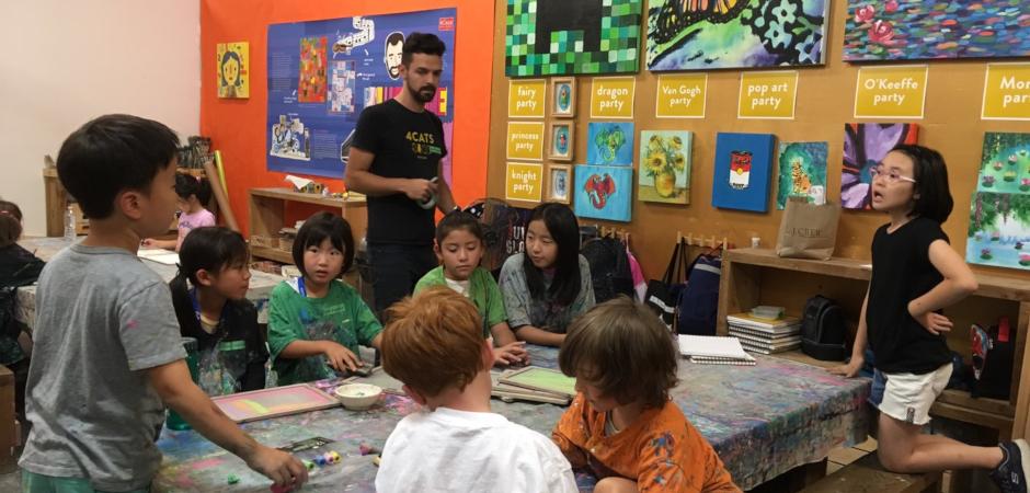 お絵かき教室で外国の先生と学ぶ子供たち