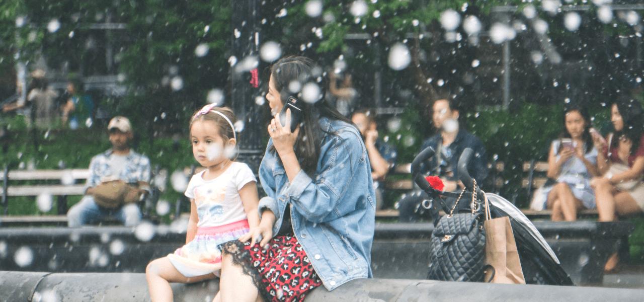 子供と一緒に噴水の前に座っているシンママ