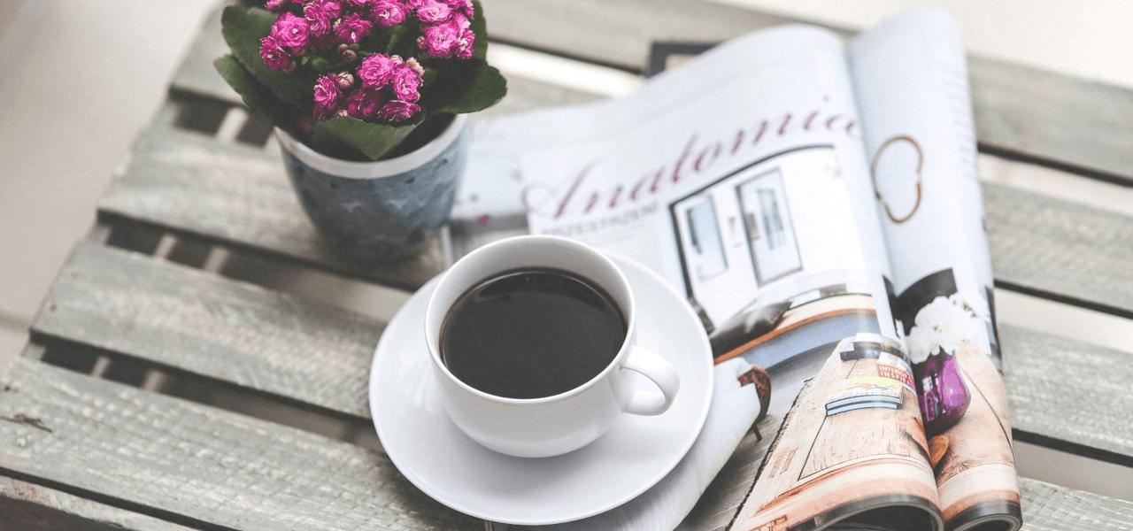 雑誌の横に置かれたコーヒーで経費を連想する