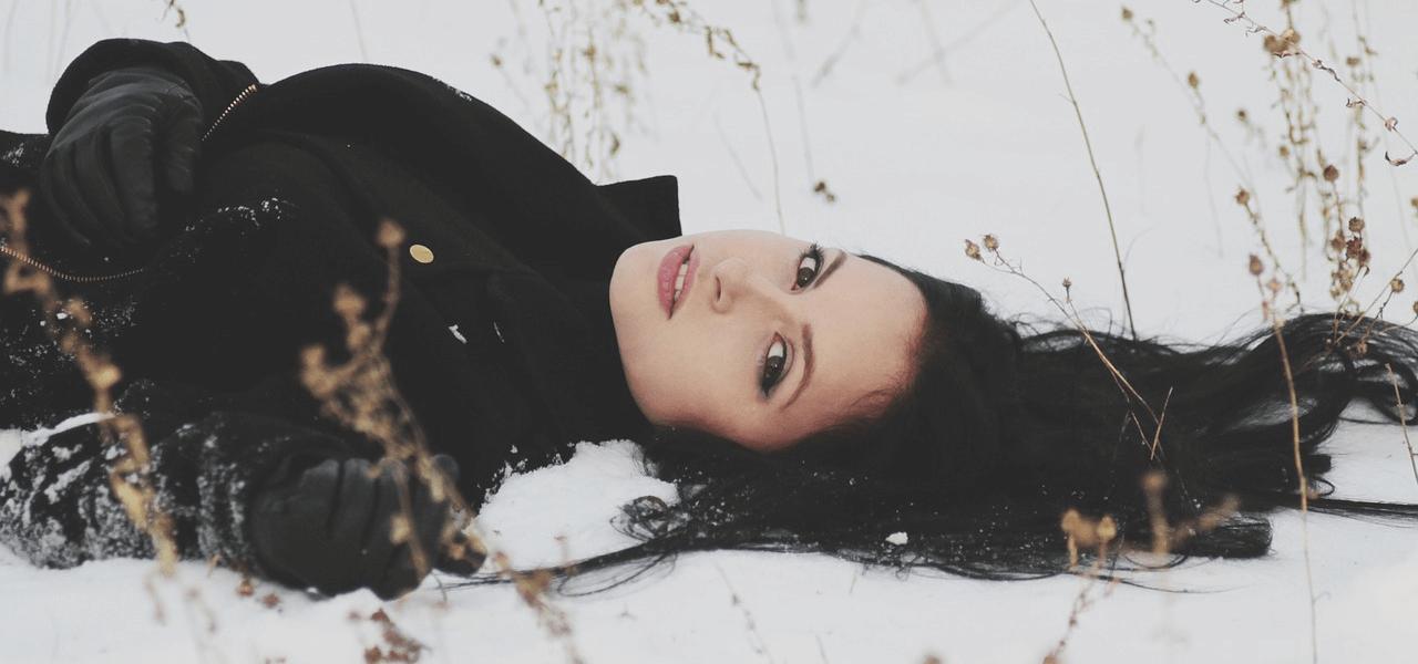 雪の中で横になる女性