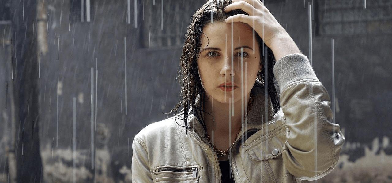 雨の中で考えている女性