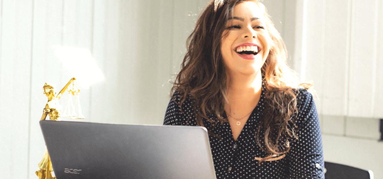 笑顔でパソコンの前に座る女性
