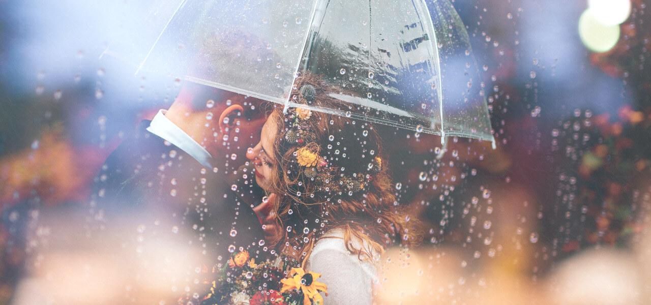 雨の中で寄り添う外国人カップル