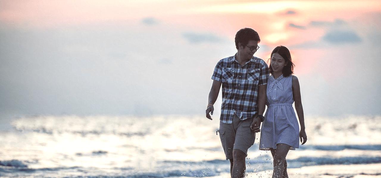 手を取り合って浜辺を歩くカップル