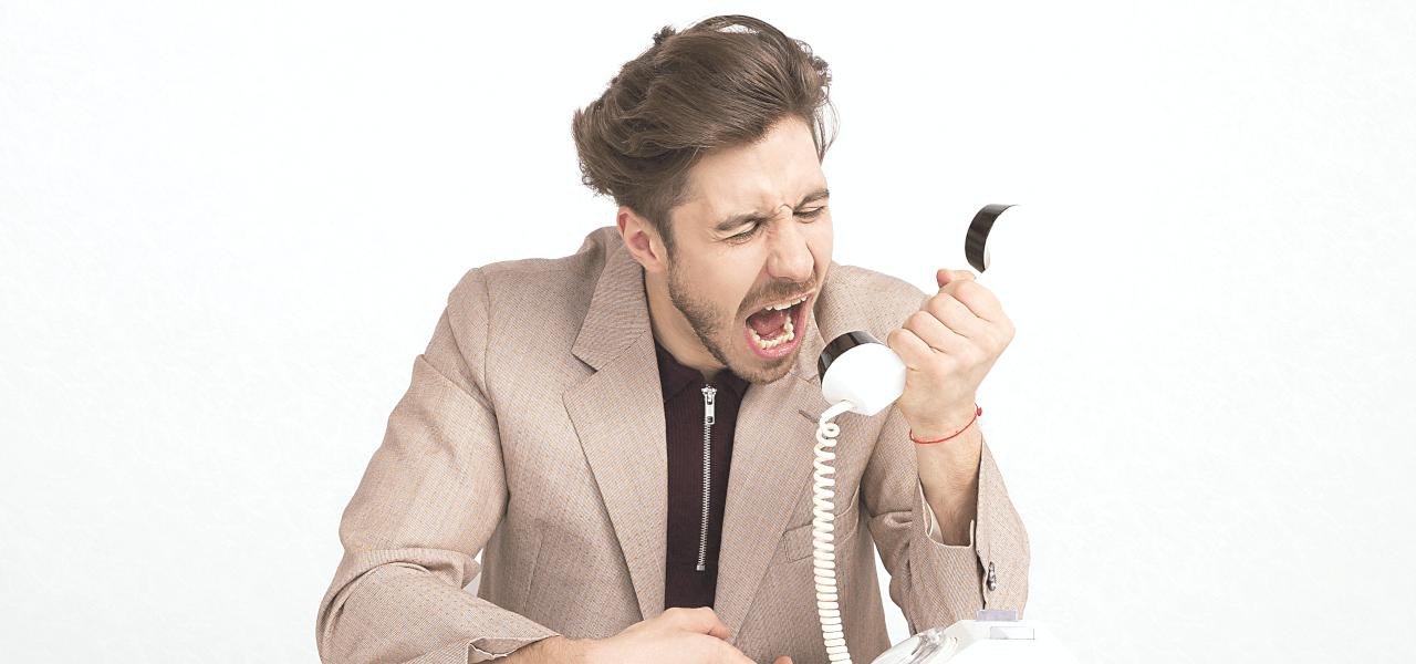 受話器に向かって叫んでいる外国人男性