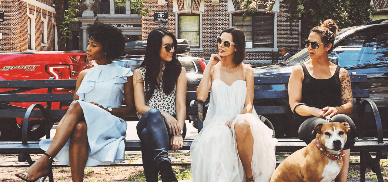 様々なファッションの女性が一緒にベンチに座っている様子