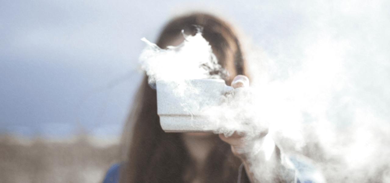 湯気の出ているカップを持つ女性