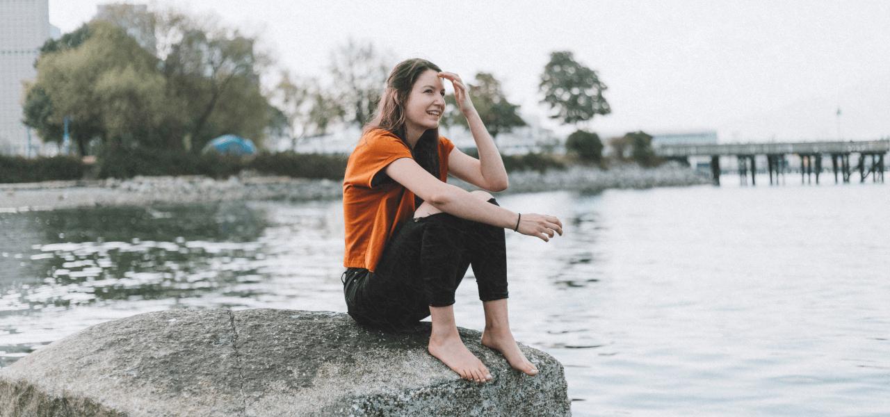 海外の石の上で将来を考える女性