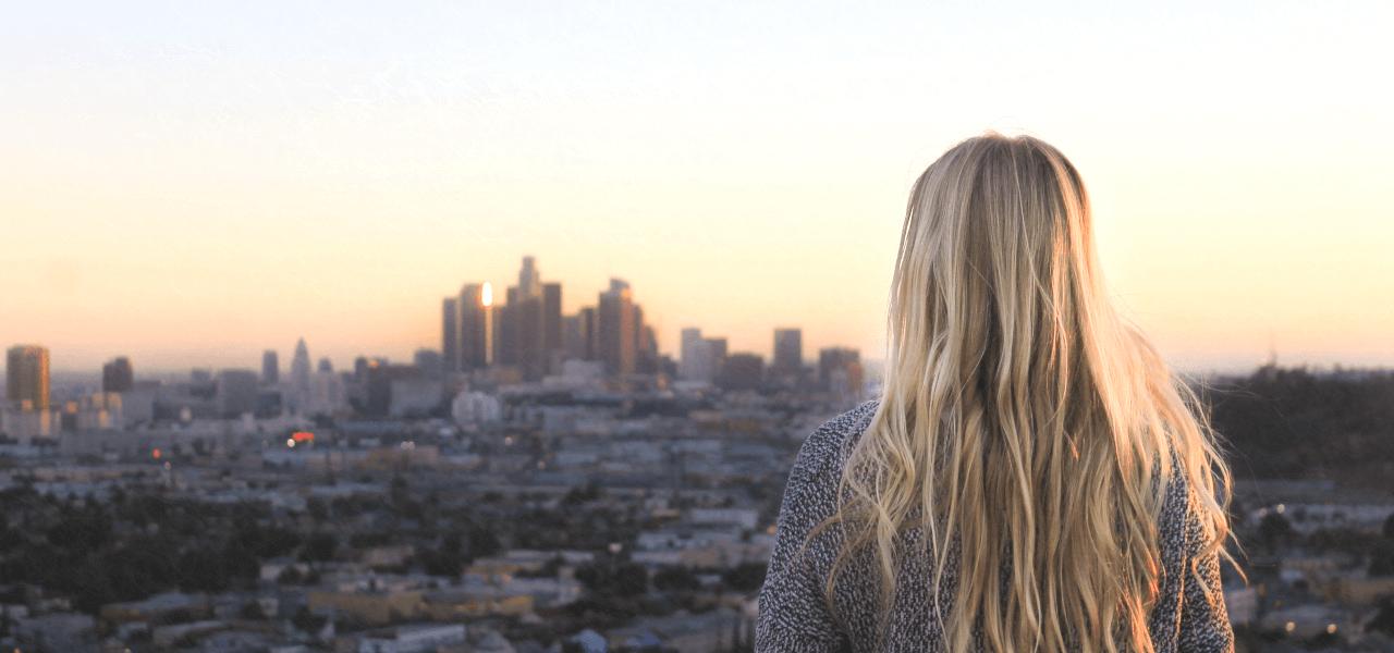 高台の上から夕暮れの街を見つめる外国の女性