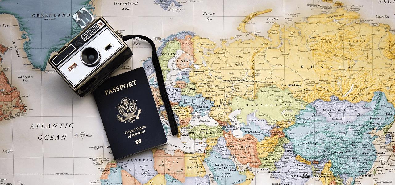 世界地図の上で広げられたパスポート