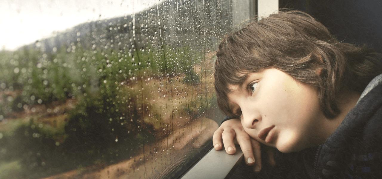 外が雨で遊べない外国の男の子