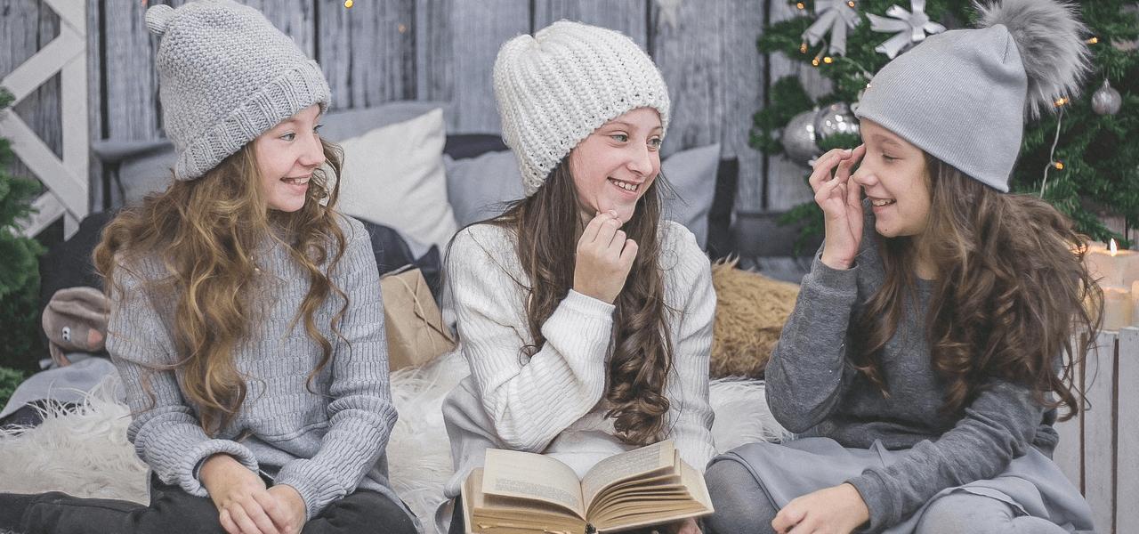 3人の女の子が楽しく本について話している様子