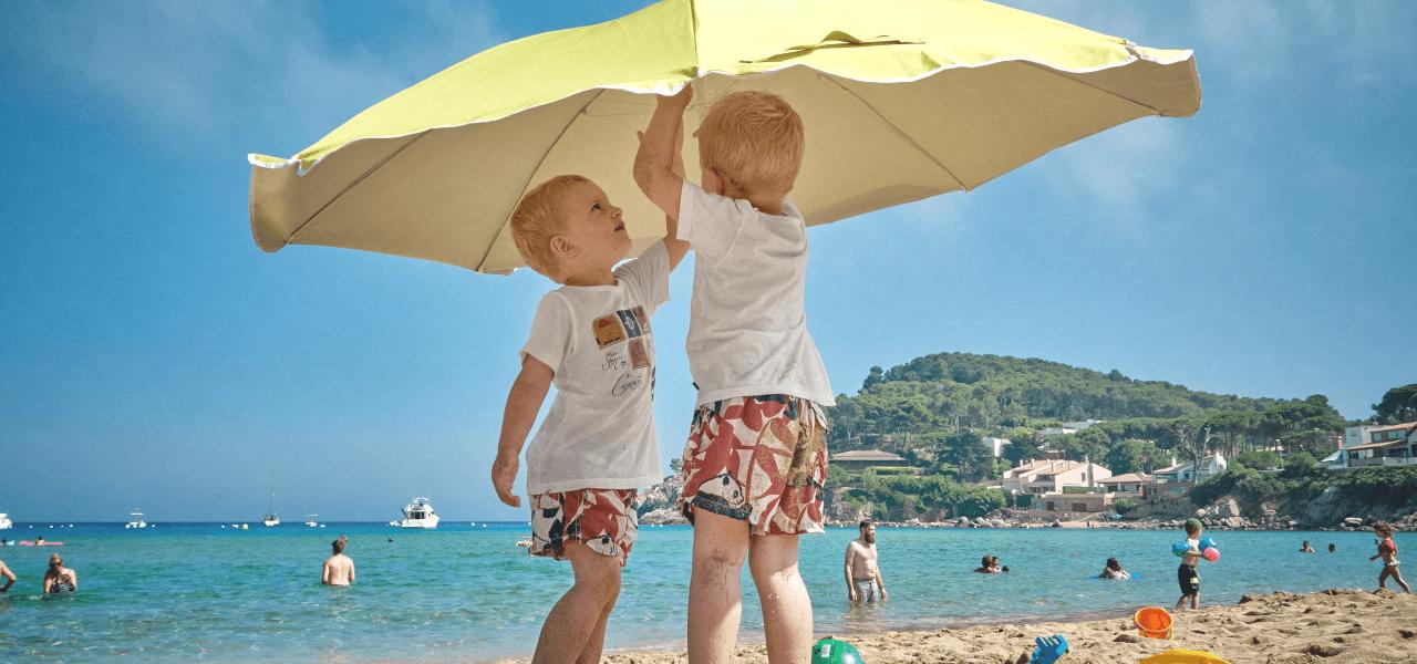 2人の海外の子供たちがビーチでパラソルを直す様子