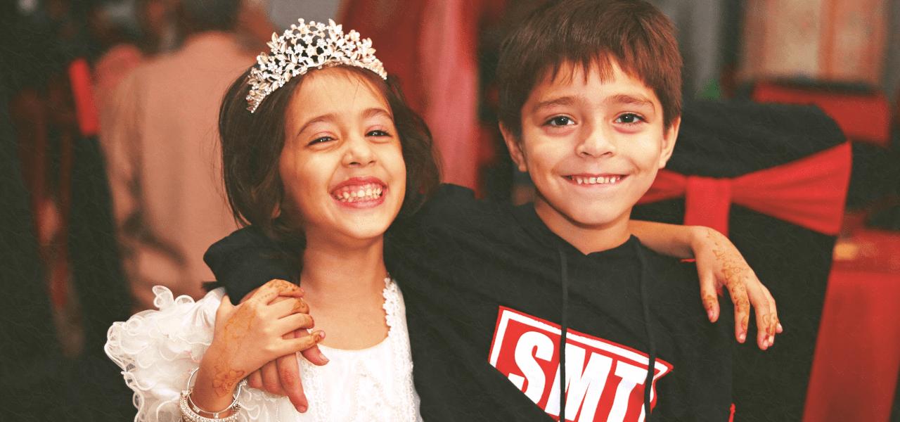海外の小学生の男の子と女の子が肩を組んで笑顔で笑っている様子