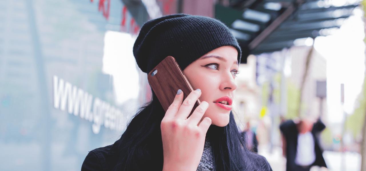 学校にスマートフォンで電話をかけている女性