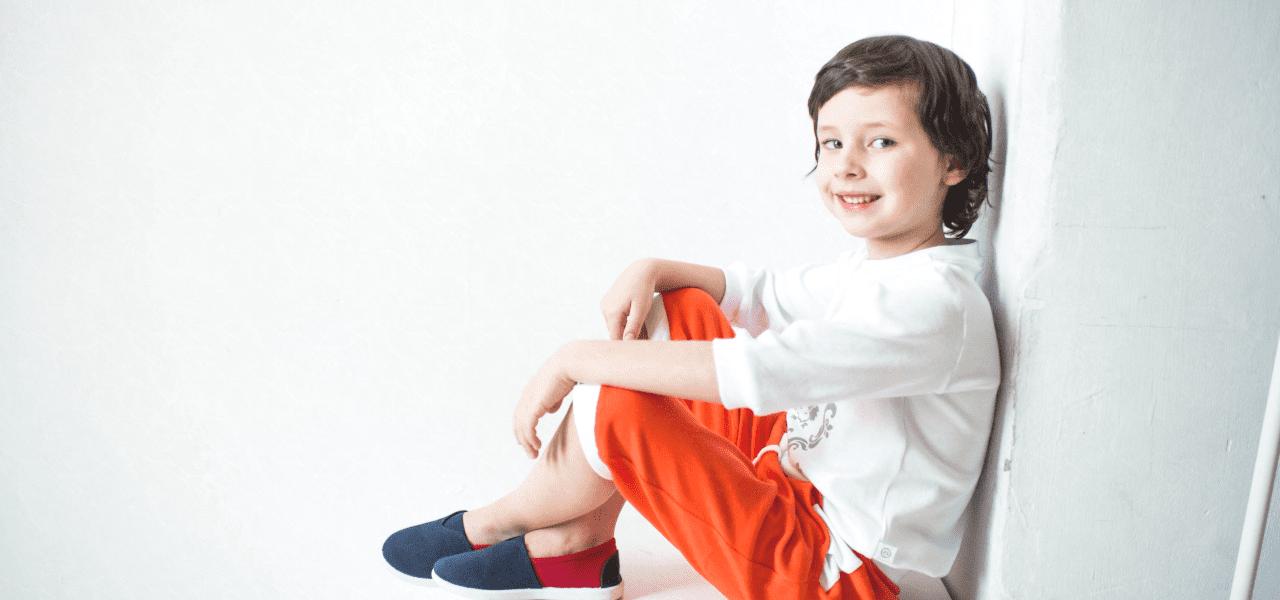 笑顔で壁に腰掛ける男の子
