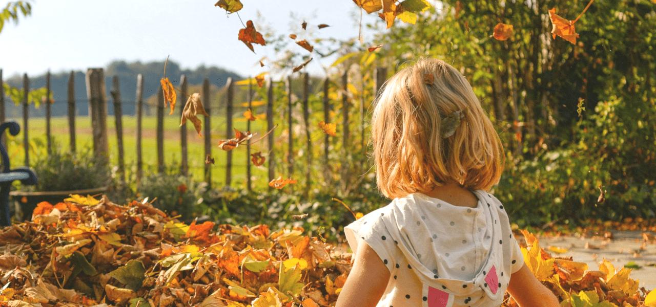 落ち葉の前に立っている女の子