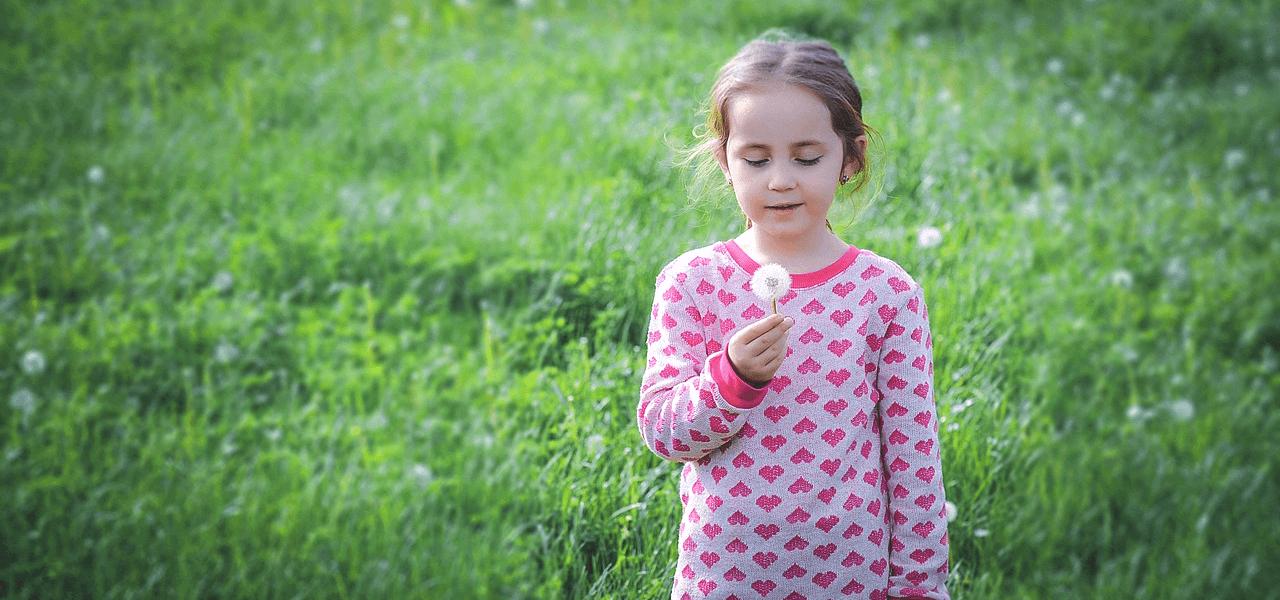 たんぽぽの綿毛で遊ぶ外国人の女の子