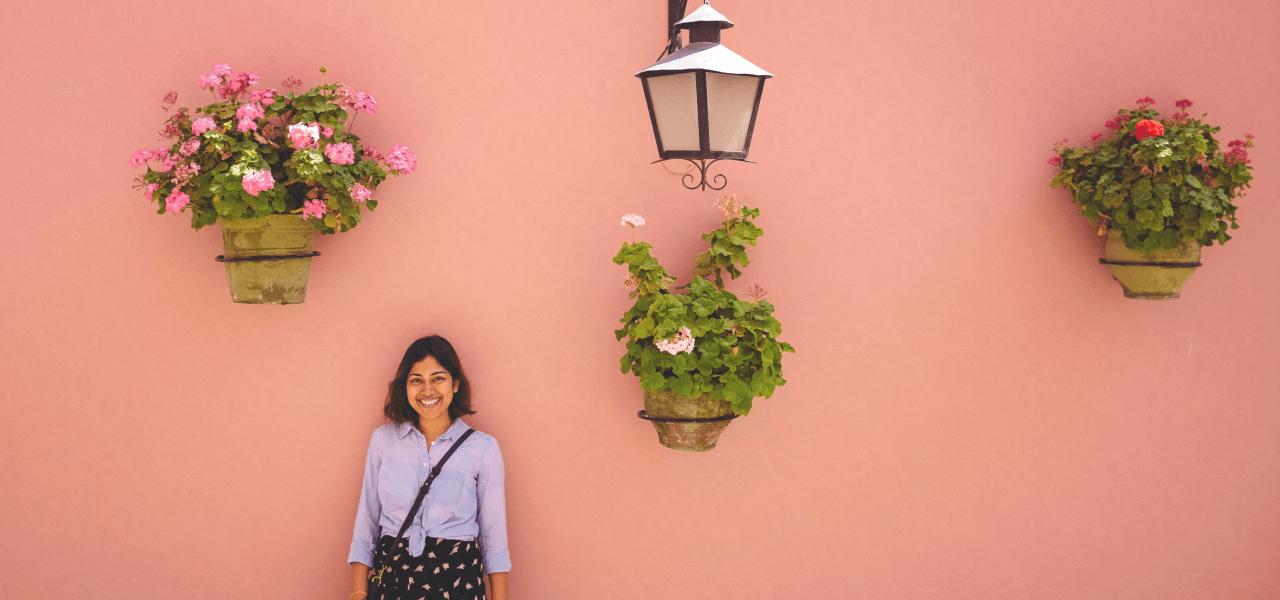 ピンク色の壁の前で写真を撮っている留学生の女の子