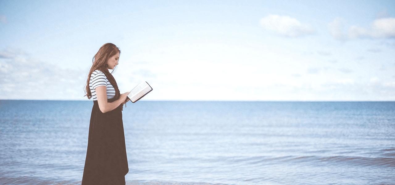 海で本を読む外国の女性