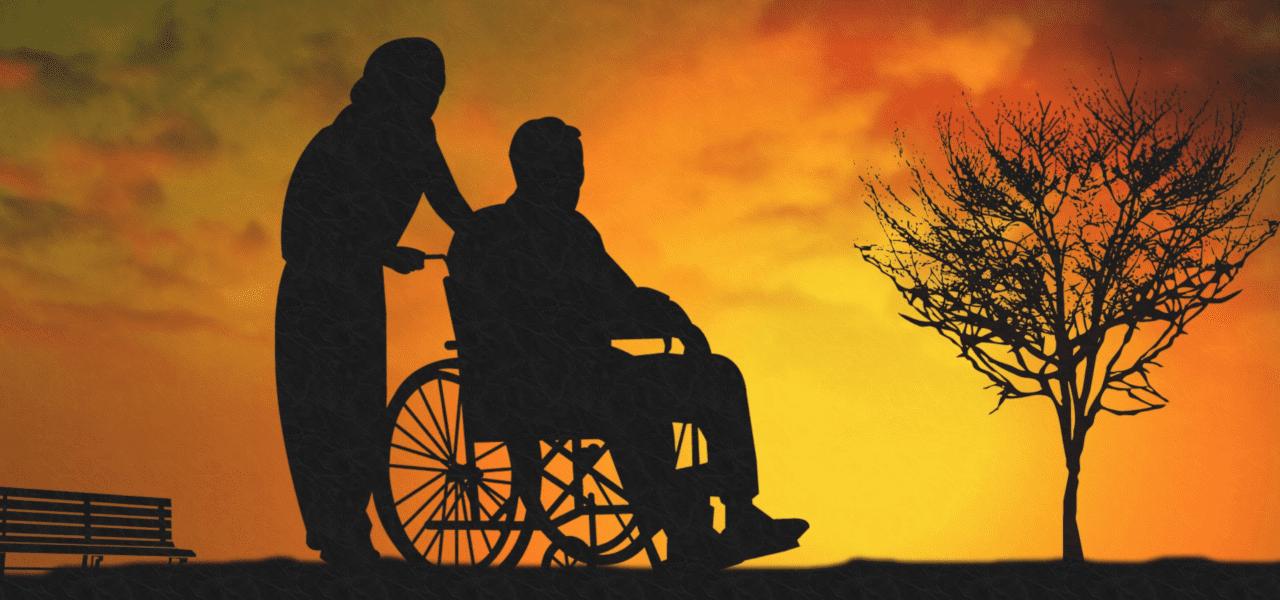おじいさんが車いすに乗って介護士がエスコートする様子