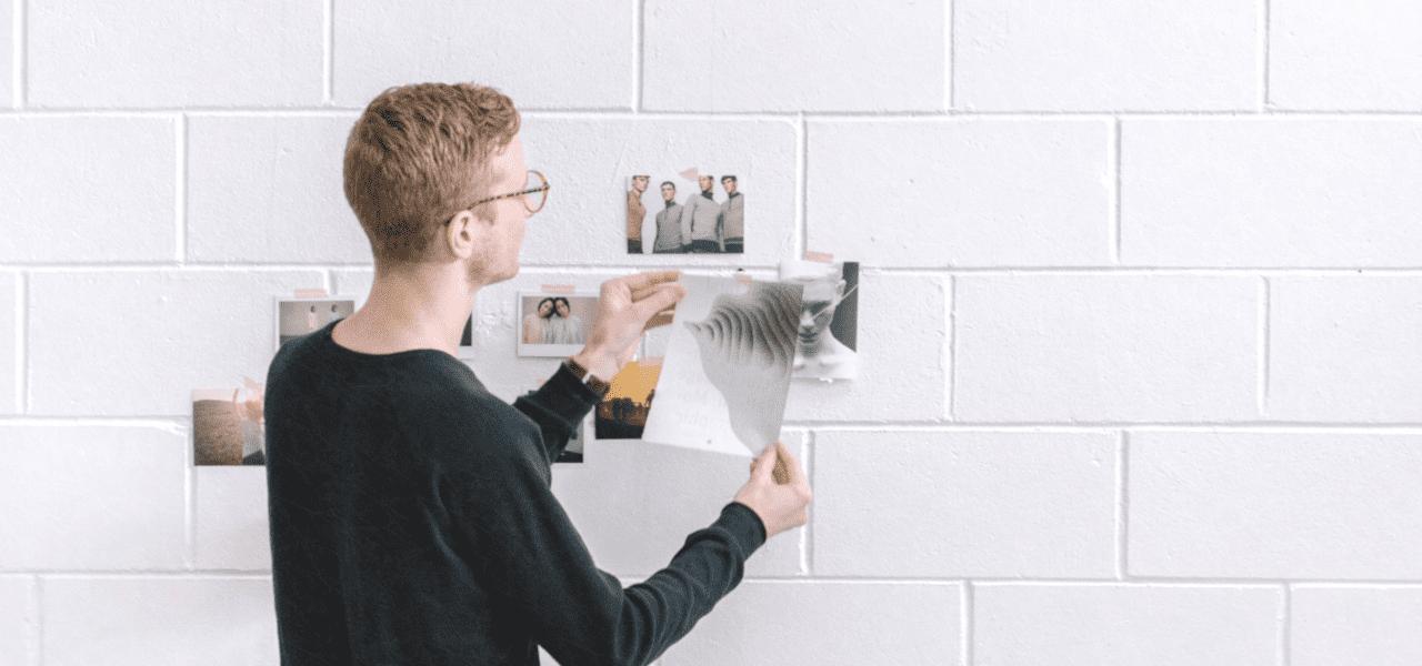 壁に写真を張り付けるデザイナー