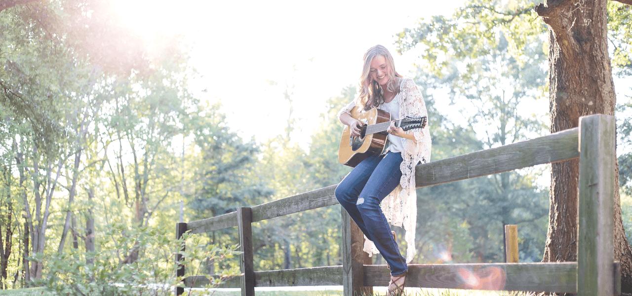 桟橋でギターを弾きながら楽しんでいる外国の女性