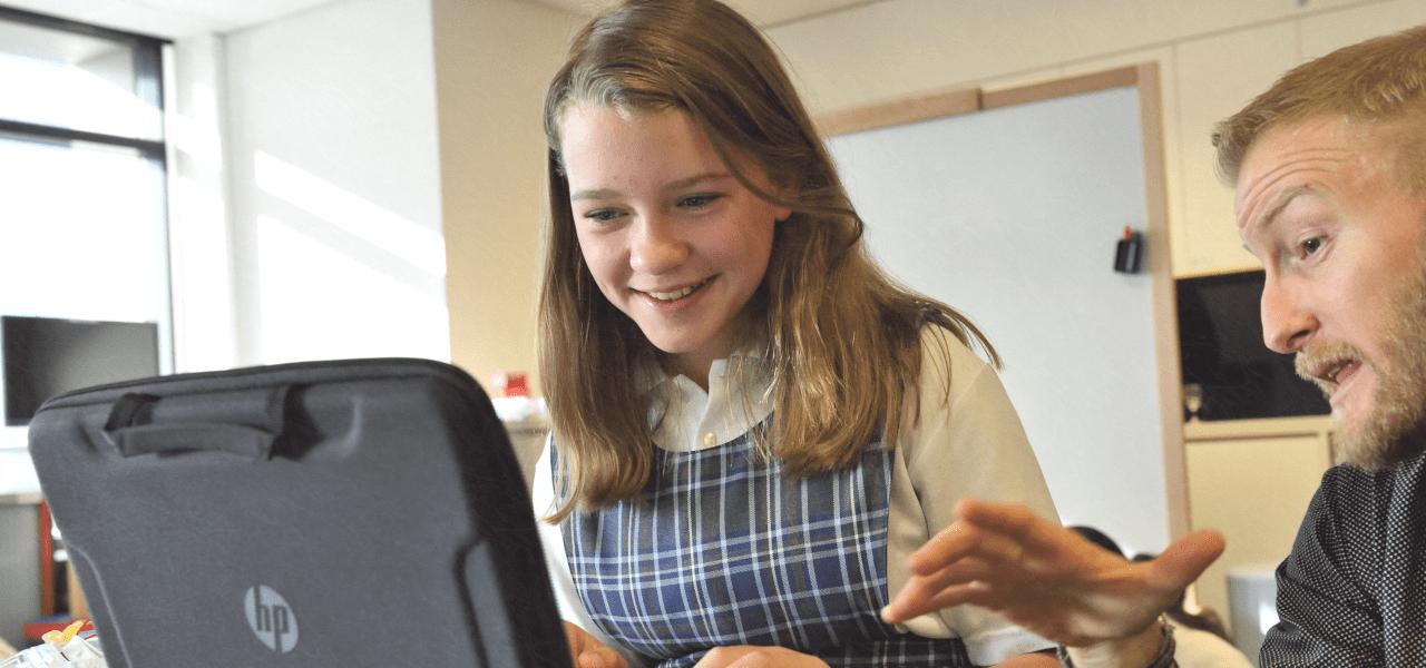 外国の子供に先生がパソコンを教えている様子