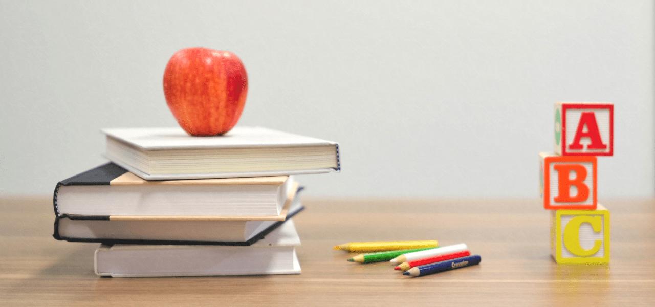 ABCと書かれた本の上のリンゴ