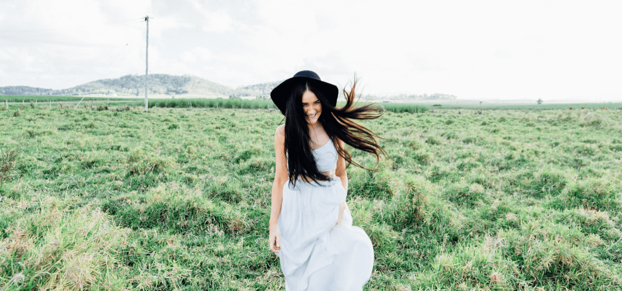 草原に笑顔でたたずむ女性