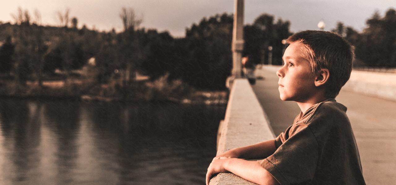 橋のたもとで夕暮れを見つめる男の子