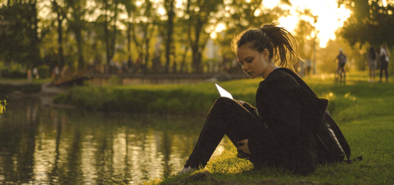 川のほとりで勉強する大学生