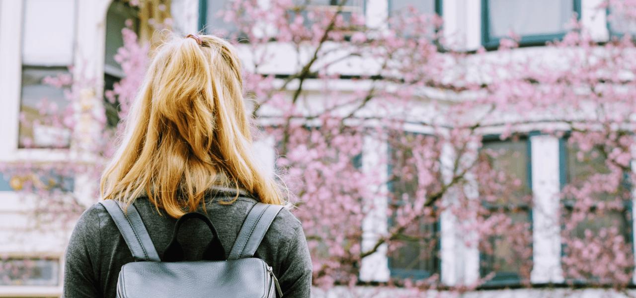 春の入学シーズンで桜を見つめる女性