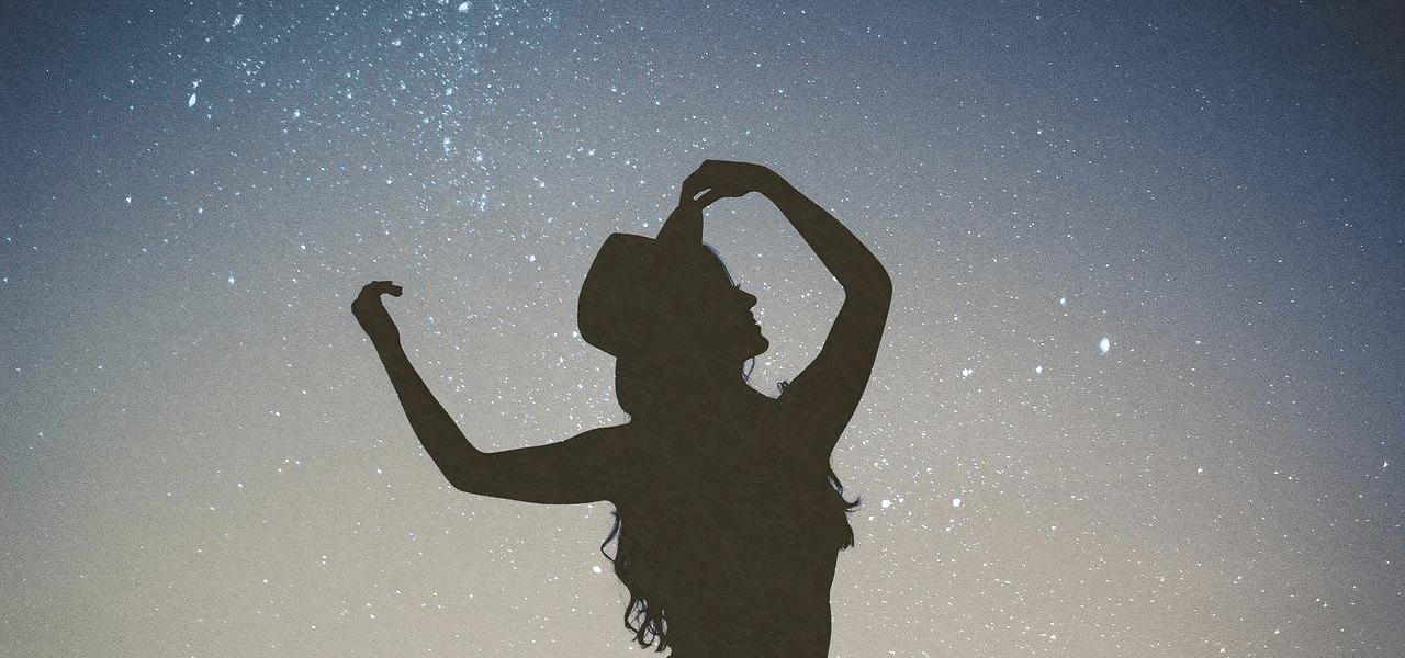 満点の星空の元でポーズをとる女性