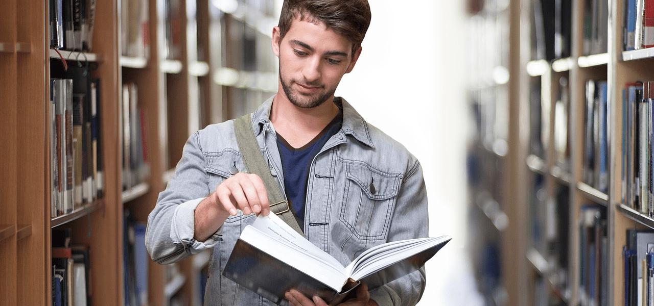 外国の男子大学生が図書館で学ぶ様子