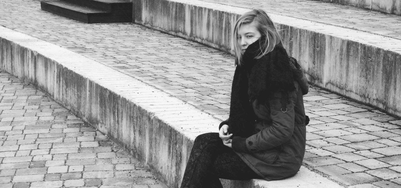 寒そうに肩をすぼめる女性